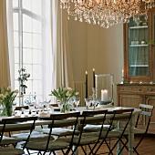 Frühlingshaft gedeckter Esstisch mit Tulpen und antiker Geschirrschrank im Esszimmer mit raumhohen Fenstern