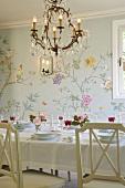 Romantisches Ambiente im Esszimmer mit floraler Wandmalerei und gedecktem Esstisch