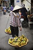 Vietnamese woman carrying bananas in 'don ganh' (carrying yoke)