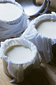 Cheese-making: curd in muslin cloths in round moulds