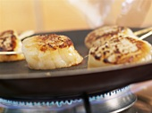 Frying scallops on small skewers in a frying pan