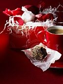 Sesame chocolate truffles in gift wrapping, cup of coffee