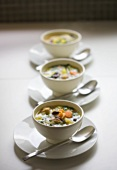 Hearty soup with vegetables, noodles and meat in soup cups