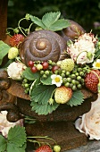 Summer decoration: snail shells, berries & roses in rusty vase
