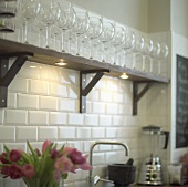 Wine glasses on wooden shelf in a kitchen