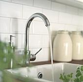 Wasser fliesst in ein modernes Keramikspülbecken