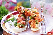 Prawn, vegetable and bacon kebabs on baguettes