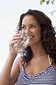 Young woman drinking a glass of mineral water