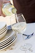 Weisswein wird in ein Glas eingeschenkt