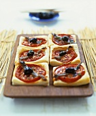 Puff pastry slices with tomatoes, olives and anchovies