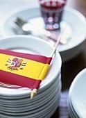 Deko für ein spanisches Fest: Fähnchen auf einem Tellestapel