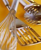Kitchen utensils: whisk, spatula, pasta tongs