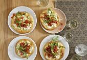 Four mini-pizzas topped with sheep's cheese, tomato & rocket