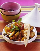 Tajine of Jerusalem artichokes and a piece of pita bread