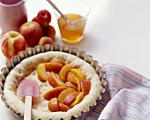 Uncooked dough topped with peach slices in a baking tin,