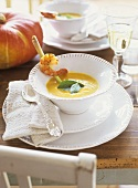 Pumpkin & coconut soup garnished with prawn on lemon grass