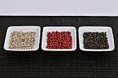 Black, red and white peppercorns in three dishes