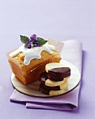 Iced cake with candied violet, chocolate-dipped biscuits