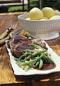 Braised leg of lamb with beans and bacon and potato dumplings
