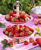 Fresh strawberries on a tiered stand on a garden table