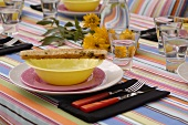 Place-setting with bread stick on summery table
