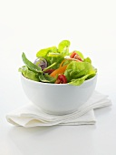 A small bowl of green salad with vegetables and basil