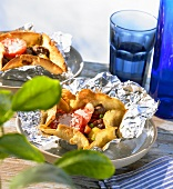 Lamb Kleftiko in foil with tomatoes and melted cheese
