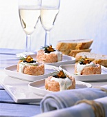 Four portions of salmon tartare on plates, glasses of sparkling wine