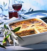 Moussaka in a baking dish and a glass of red wine