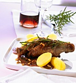 Lamb shank with pine nuts, pomegranate sauce and potatoes