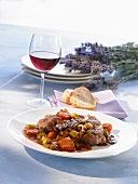 A slice of ossobuco with braised vegetables & a glass of wine