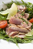 Sliced, grilled tuna on rocket salad with tomato