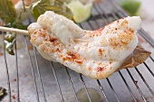 Ein Saltimbocca-Spießchen von der Seezunge mit Chilipulver