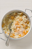 Pumpkin risotto in aluminium pan with spoon
