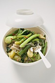 Noodles and vegetables in Asian soup bowl