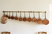 Copper pans of various sizes hanging on a rail