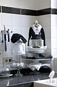 Küchenausschnitt mit Utensilien und Dekorationsobjekten in Schwarz und Weiss auf schwarzer Arbeitsplatte