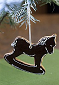 Rocking horse tree ornament hanging on a fir branch