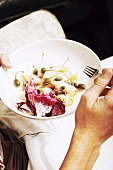 Man eating salad with capers and radicchio