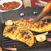 Brushing chicken breasts in a grill frying pan with marinade