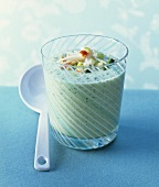 Cold, frothy cucumber soup in glass with crab salad