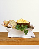 Herb bread with orange cheese spread in a dish