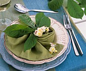 Place-setting with chestnut flowers and leaf