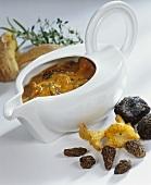 Eine Sauciere mit Pilzrahmsauce und frischen Pilzen