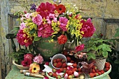 Vase of flowers and strawberries out of doors