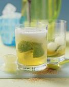 Zwei Gläser Caipirinha-Bowle mit Melonenkugeln