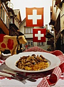 Zurich-style veal with rösti, row of Swiss houses