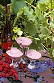 Raspberry cream in three glasses with a bottle of dessert wine