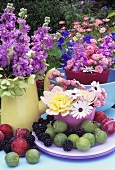 Vases of summer flowers with fruit out of doors