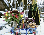 Dougnuts, champagne and tulips on snow-covered table